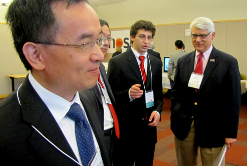 Michael Song, left, IEI executive director, Bloch School Dean Teng-Kee Tan, and Bank of Blue Valley President Bob Regnier (far right) talk with a student showcasing at VCC.