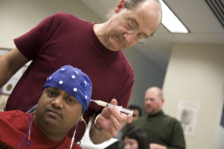Jesse Sherwood, graduate research assistant and Ph.D. student, preps electrical engineering student Ramaraju Medisetty by injecting a conductive gel into the electrodes of the brain wave cap.